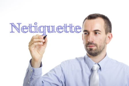 Netiquette - Young businessman writing blue text on transparent surface - horizontal image