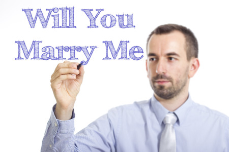 Will You Marry Me - Young businessman writing blue text on transparent surface - horizontal image