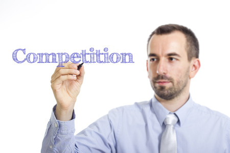 Competition - Young businessman writing blue text on transparent surface - horizontal image