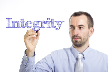 Integrity - Young businessman writing blue text on transparent surface - horizontal image
