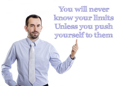 You will never know your limits Unless you push yourself to them - Young businessman with small beard pointing up in blue shirt - horizontal image