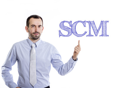 SCM (Supply Chain Management) - Young businessman with small beard pointing up in blue shirt - horizontal image