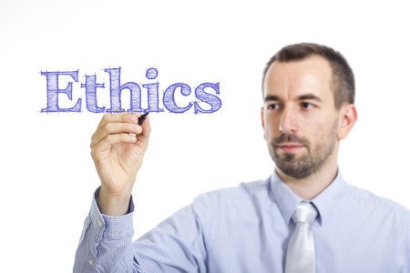 Ethics - Young businessman writing blue text on transparent surface - horizontal image