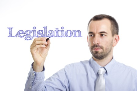 lawmaking: Legislation - Young businessman writing blue text on transparent surface - horizontal image Stock Photo