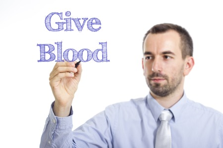 transfused: Give Blood - Young businessman writing blue text on transparent surface - horizontal image Stock Photo