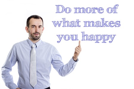 Do more of what makes you happy - Young businessman with small beard pointing up in blue shirt - horizontal image Stock Photo