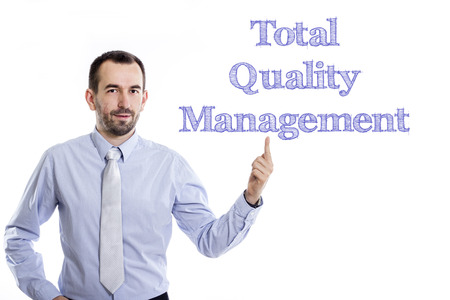 Total Quality Management - Young businessman with small beard pointing up in blue shirt - horizontal image
