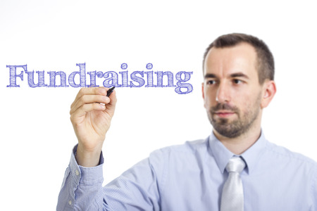 Fundraising - Young businessman writing blue text on transparent surface - horizontal image