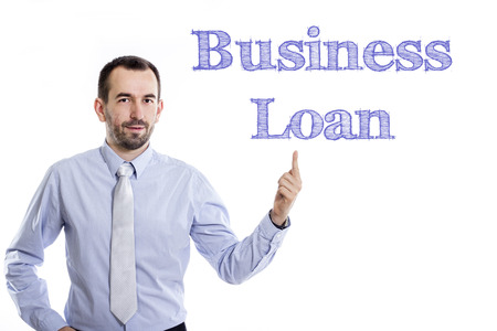 borrowing: Business Loan - Young businessman with small beard pointing up in blue shirt - horizontal image