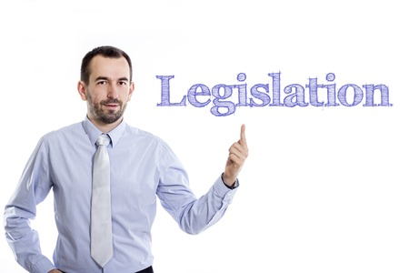 lawmaking: Legislation - Young businessman with small beard pointing up in blue shirt - horizontal image Stock Photo