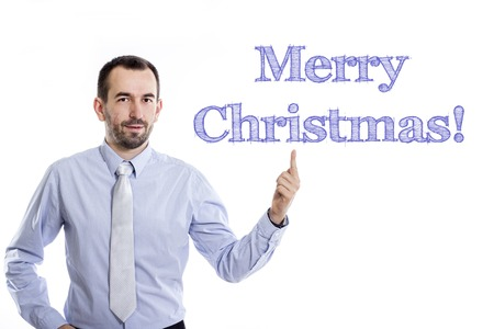 Merry Christmas!  Young businessman with small beard pointing up in blue shirt - horizontal image