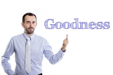 goodness: Goodness - Young businessman with small beard pointing up in blue shirt - horizontal image