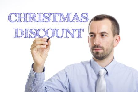 Christmas Discount Jeune homme d'affaires écrit un texte en bleu sur une surface transparente - image horizontale Banque d'images - 73122344