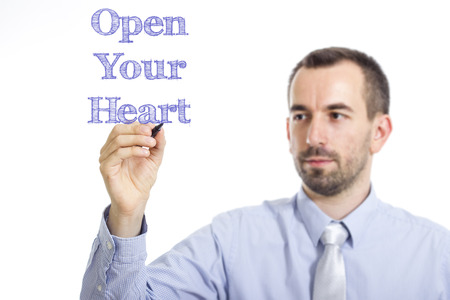 Open Your Heart - Young businessman writing blue text on transparent surface - horizontal image