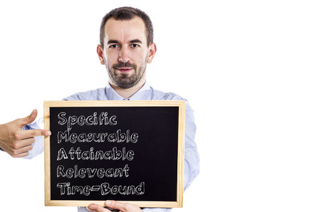 specific: Specific Measurable Attainable Releveant Time-Bound SMART - Young businessman with blackboard - isolated on white - horizontal image Stock Photo