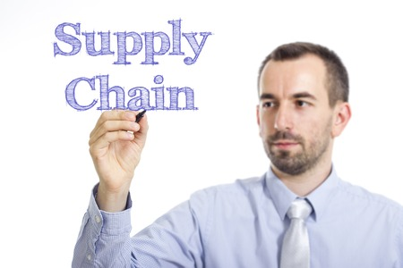 scm: Supply Chain - Young businessman writing blue text on transparent surface - horizontal image Stock Photo