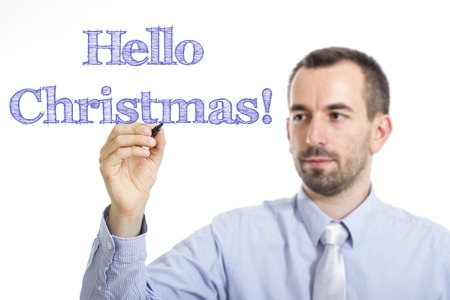 Hello Christmas Young businessman writing blue text on transparent surface - horizontal image Banque d'images