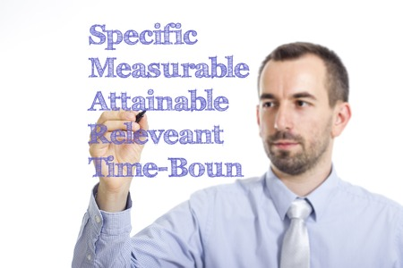 specific: Specific Measurable Attainable Releveant Time-Bound SMART - Young businessman writing blue text on transparent surface - horizontal image