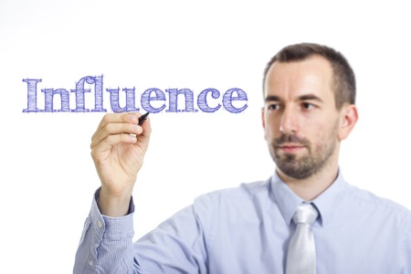 Influence - Young businessman writing blue text on transparent surface - horizontal image