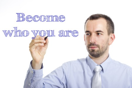 be the identity: Become who you are - Young businessman writing blue text on transparent surface - horizontal image