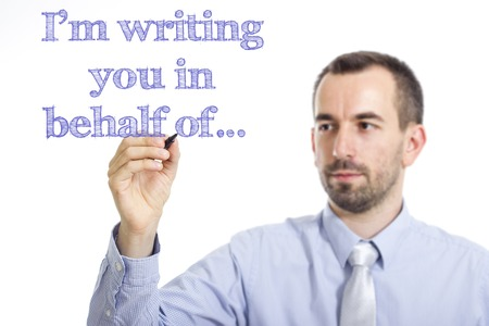 I'm writing you in behalf of…  - Young businessman writing blue text on transparent surface - horizontal image