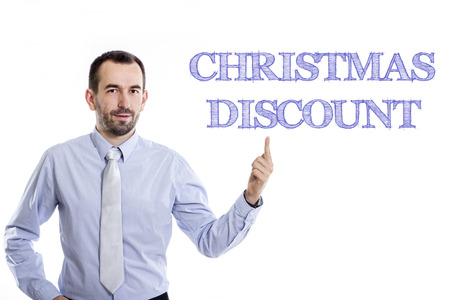 Christmas Discount  Young businessman with small beard pointing up in blue shirt - horizontal image Banque d'images