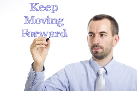 Keep Moving Forward - Young businessman writing blue text on transparent surface - horizontal image