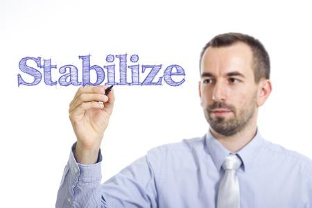 Stabilize - Young businessman writing blue text on transparent surface - horizontal image Stock fotó