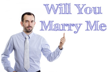 Will You Marry Me - Young businessman with small beard pointing up in blue shirt - horizontal image