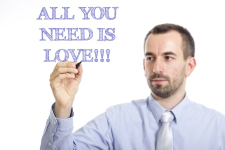 All you need is love!!! Young businessman writing blue text on transparent surface - horizontal image