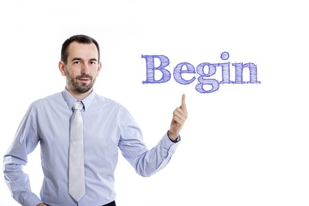 variance: Begin - Young businessman with small beard pointing up in blue shirt - horizontal image