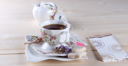 A cup of tea and cookies on wooden table photo