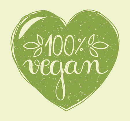 Hand lettering of the text 100 percent vegan in a hand drawn green heart with grunge stamp effect.