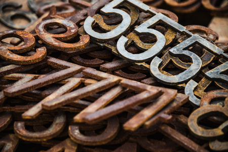 Piles of rusty metal numbers and letters