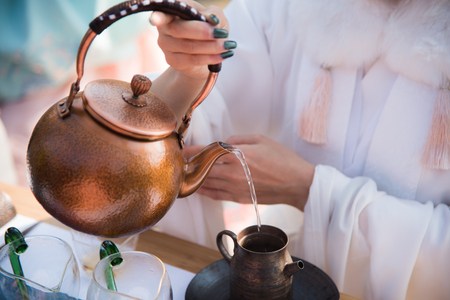 A young woman performs a tea ceremony. She is making tea with boiled water. Фото со стока