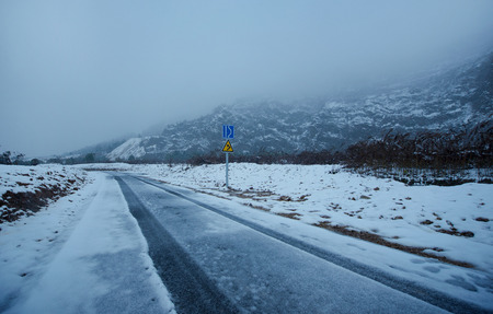 After the snow, the road at the foot of the mountain.