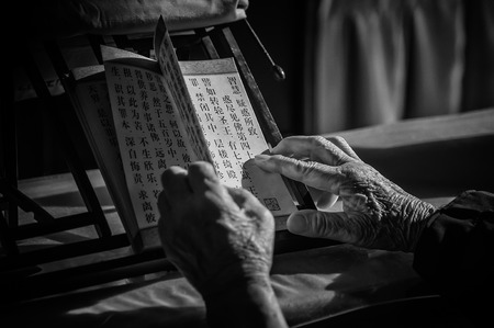 Wuxi, JiangsuChina - September 03, 2016: An old man was reading Buddhist scriptures.
