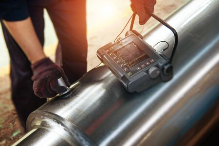 Technicians use flaw detectors to detect cracks or defects in metal pipes Фото со стока
