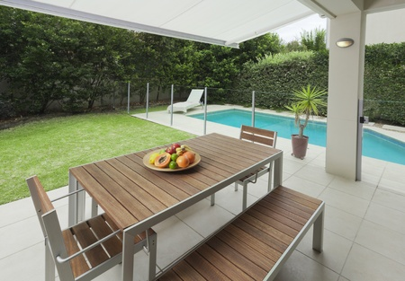 chair garden: Modern suburban backyard with table setting and swimming pool