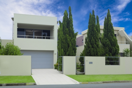 Modern multilevel house front with double garage, pine trees and lawn photo