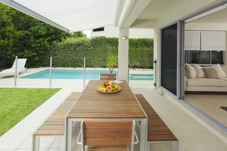 sunbed: Modern suburban backyard and living room with table setting and swimming pool Stock Photo