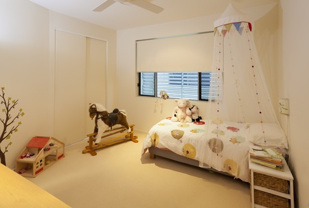 Little girls bedroom with bed, rocking horse, toys and books photo