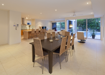 Wooden dining table and kitchen in a modern house overlooking the backyard and swimming pool