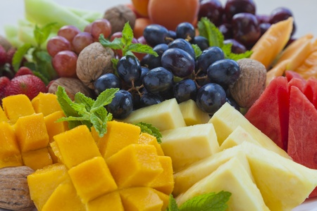 fruit platter: Colorful summer fruit platter with mango, pineapple, watermelon, grapes, cherries, apricots, strawberries, cantaloupe, walnuts and mint Stock Photo