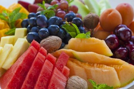 Kleurrijke zomer fruitschaal met watermeloen, meloen, druiven, kersen, abrikozen, walnoten en munt