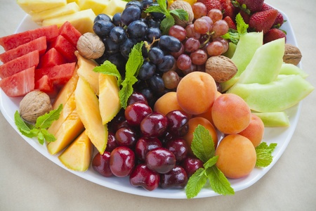 varieties: Colorful summer fruit platter with pineapple, watermelon, cherries, apricots, strawberries, cantaloupe, walnuts and mint