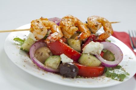 plato del buen comer: Ensalada griega tradicional con gambas picantes de chile en un pincho servido en un plato blanco