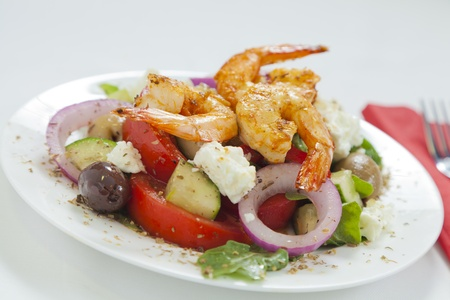 Traditional Greek salad with spicy chili prawns on a white plate Stock Photo - 12579472