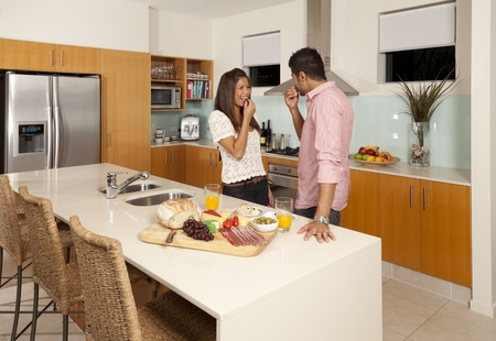 Young couple in modern kitchen with food platter photo