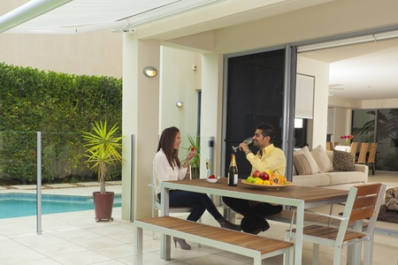 Young couple in modern backyard enjoying champagne and strawberries photo